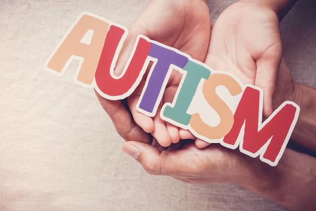 Manos sosteniendo la palabra autismo, concepto de salud mental, día mundial de concienciación sobre el autismo