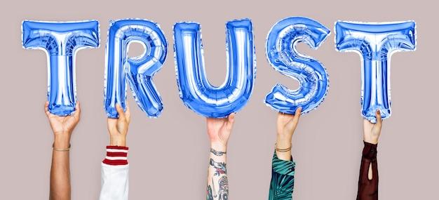 Manos sosteniendo la palabra confianza en las letras del globo