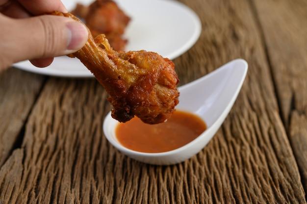 Manos sosteniendo pollo frito con salsa