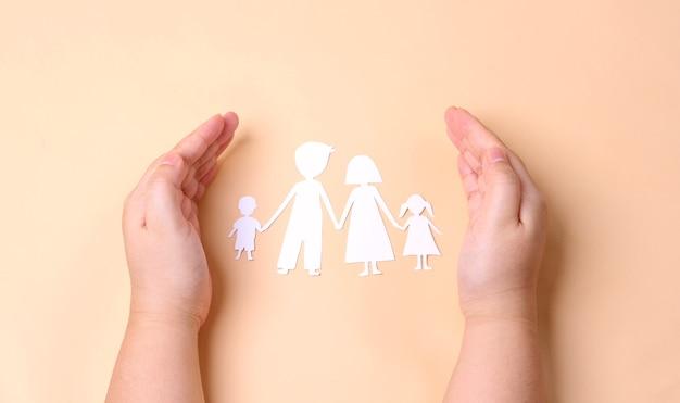 Manos sosteniendo el recorte de la familia de papel