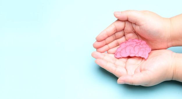 Manos sosteniendo el recorte de papel del cerebro, concepto del día mundial de la salud mental.