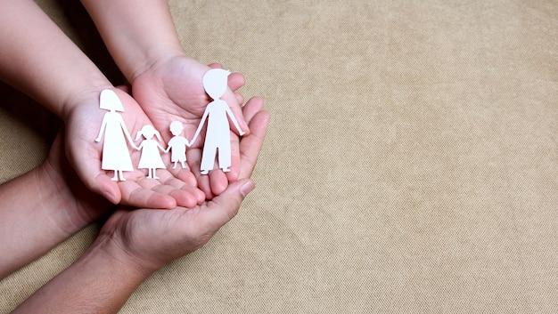 Manos sosteniendo el recorte de papel de la familia, concepto del día mundial de la salud mental.
