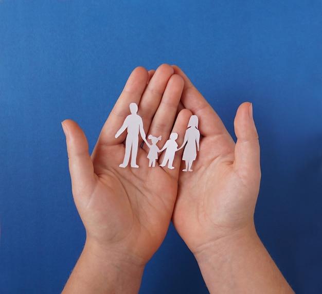 Manos sosteniendo recortes familiares de papel, concepto de distanciamiento social, covid19 en el fondo de color azul, protección familiar