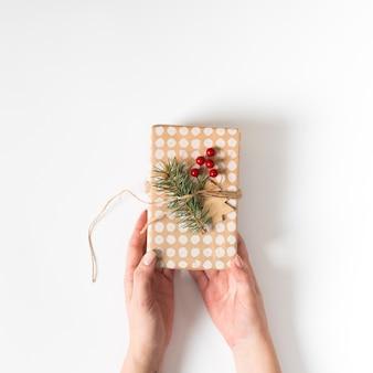 Manos sosteniendo el regalo de navidad decorado con ramita de abeto