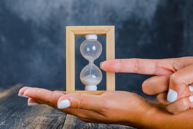 Manos sosteniendo reloj de arena y mostrando el tiempo
