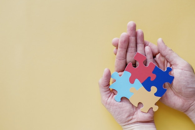 Manos sosteniendo rompecabezas, concepto de salud mental, día mundial de concienciación sobre el autismo