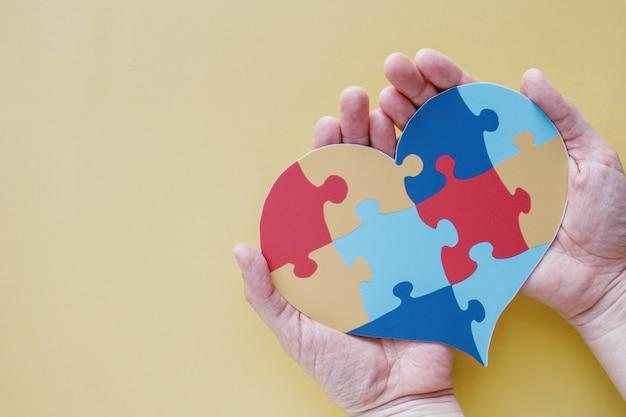 Manos sosteniendo rompecabezas corazón de rompecabezas, concepto de salud mental, día mundial de concienciación sobre el autismo, concepto de orgullo