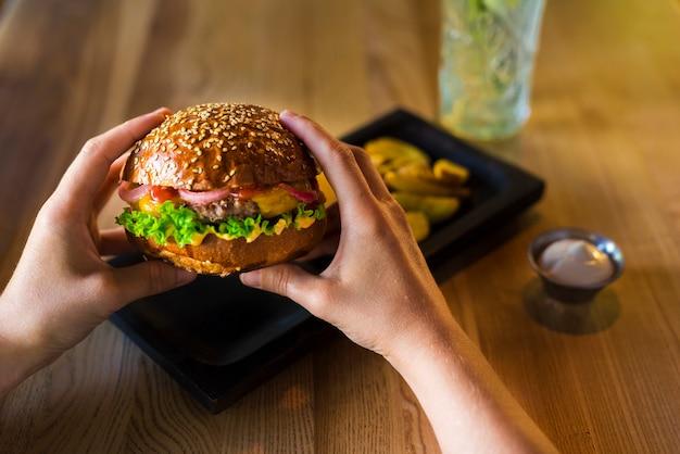 Manos sosteniendo sabrosa hamburguesa de ternera con lechuga