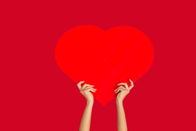 Manos sosteniendo el signo del corazón sobre fondo rojo.