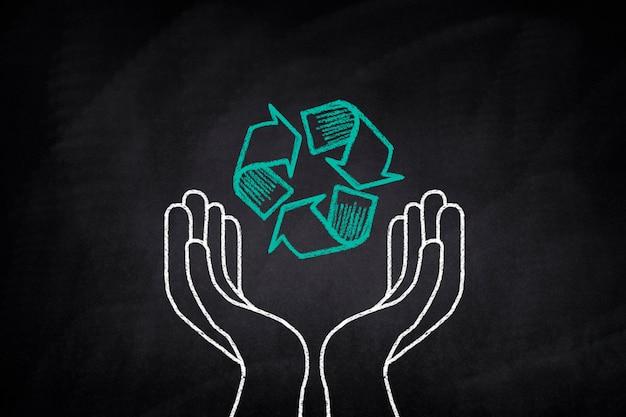 Manos sosteniendo un símbolo de reciclaje en una pizarra