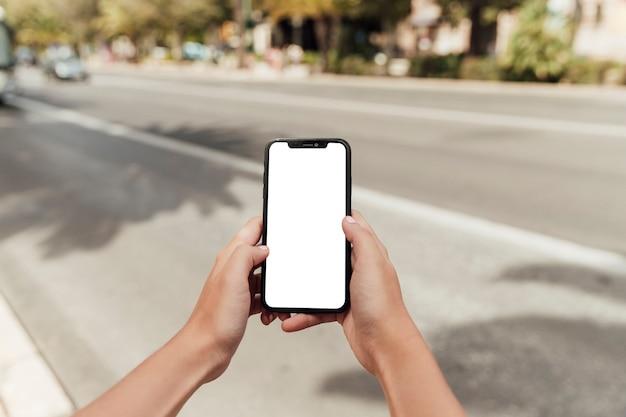 Manos sosteniendo smartphone con maqueta