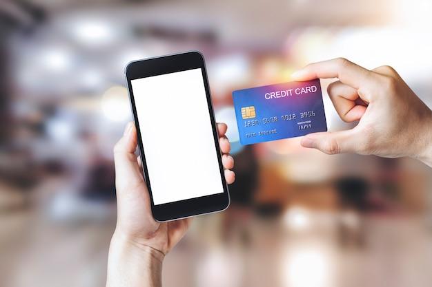 Manos sosteniendo tarjeta de crédito con teléfono móvil inteligente