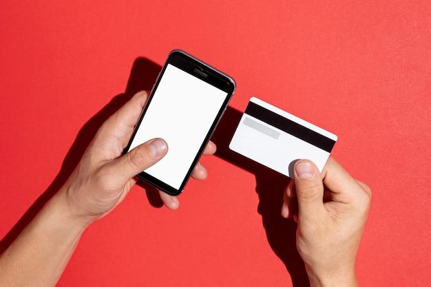 Manos sosteniendo una tarjeta de crédito y un teléfono simulacro