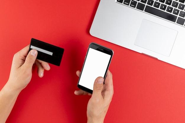 Manos sosteniendo una tarjeta negra y un teléfono simulacro