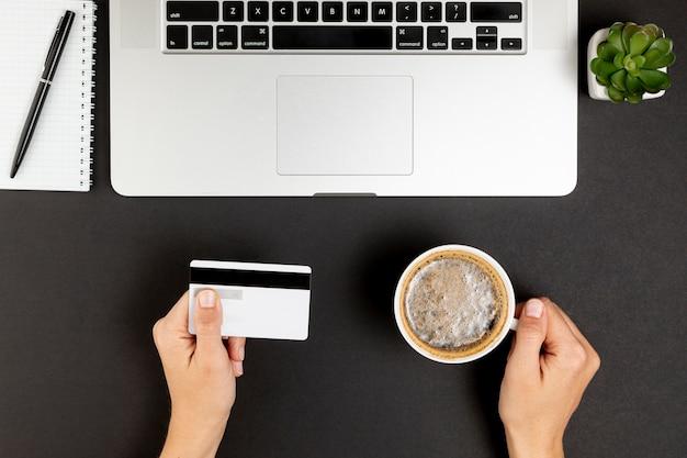 Manos sosteniendo una taza de café y una tarjeta de crédito