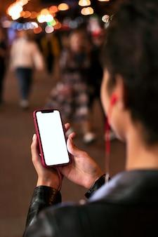 Manos sosteniendo el teléfono inteligente de cerca