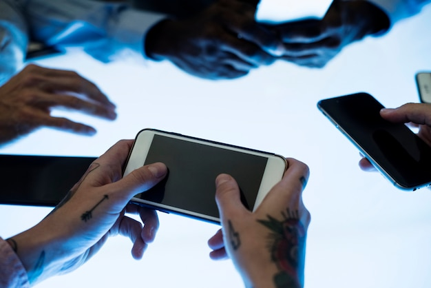 Manos sosteniendo teléfono inteligente en una reunión