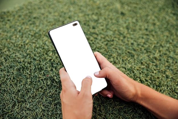 Manos sosteniendo teléfono moderno con maqueta