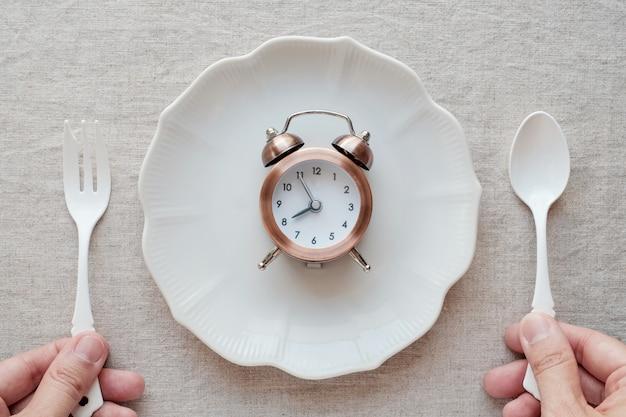 Manos sosteniendo el tenedor y la cuchara y un reloj en la placa, concepto de dieta de ayuno intermitente