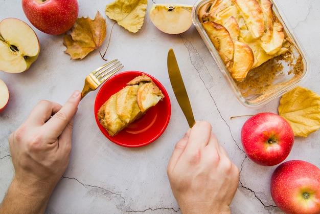 Manos sosteniendo el tenedor y el cuchillo por encima de la tarta de manzana