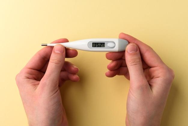 Manos sosteniendo un termómetro electrónico con temperatura normal en la pantalla sobre fondo amarillo.