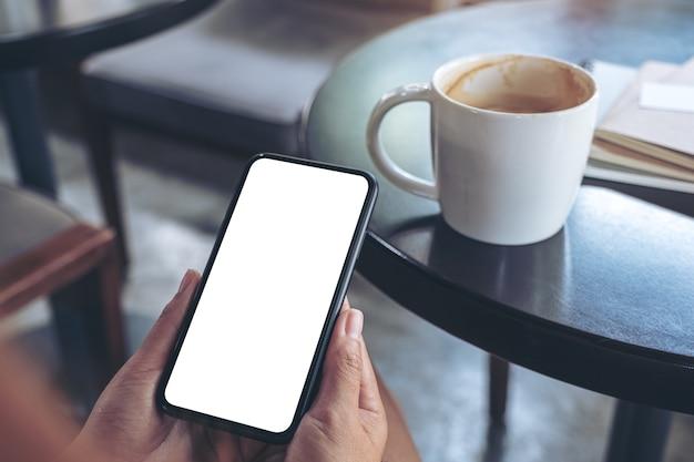Manos sosteniendo y usando un teléfono móvil negro con pantalla en blanco con taza de café en la mesa