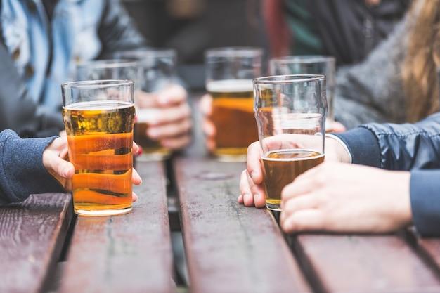 Manos sosteniendo vasos con cerveza en una mesa en londres