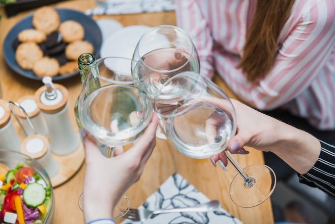 Manos sosteniendo vasos de vino juntos