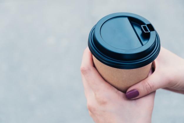 Manos sostiene café en una taza de cartón marrón con tapa negra