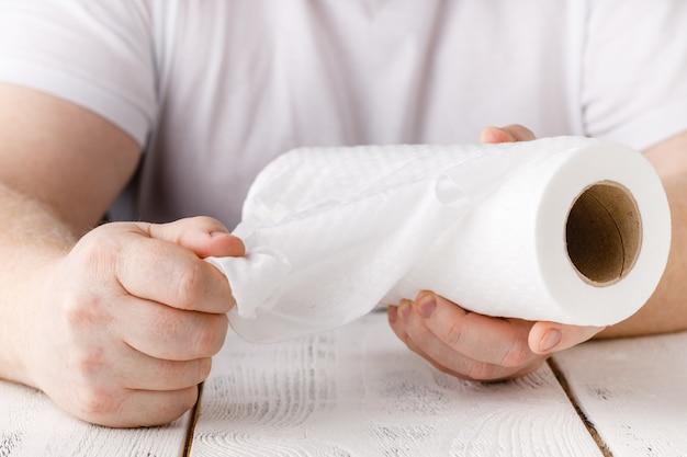 Manos sostiene el rollo de papel de cocina