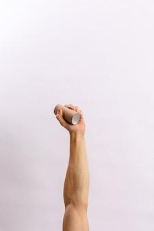 Las manos sostienen la basura sobre un fondo claro
