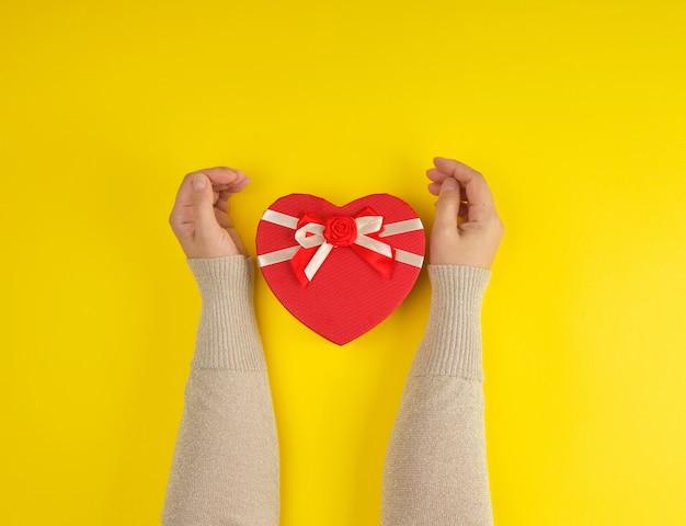 Las manos sostienen una caja roja cerrada de papel con la forma de un corazón
