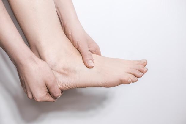 Las manos sostienen el dolor en el talón del tobillo. trauma a la articulación.