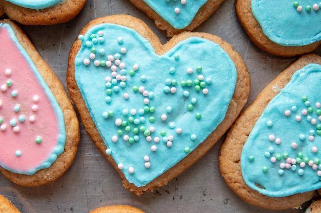 Las manos sostienen galletas de jengibre en forma de corazón