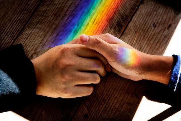 Las manos sostienen juntas con las luces prismáticas