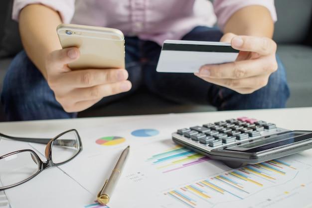 Las manos sostienen un teléfono inteligente y tarjetas de crédito para comprar en línea en el sofá de la habitación
