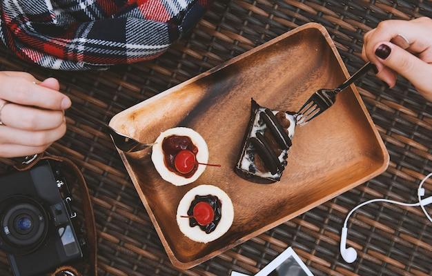 Manos sostienen tenedores comiendo tortas dulces