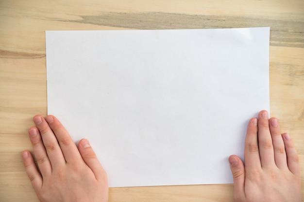 Las manos sostienen el trozo de papel en blanco blanco sobre superficie de madera.