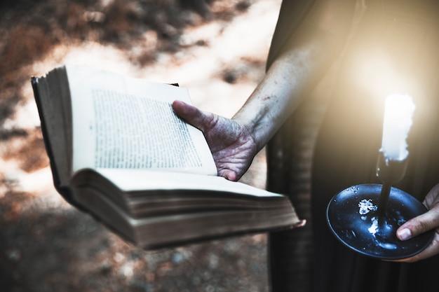Manos sucias sosteniendo el libro ritual y vela