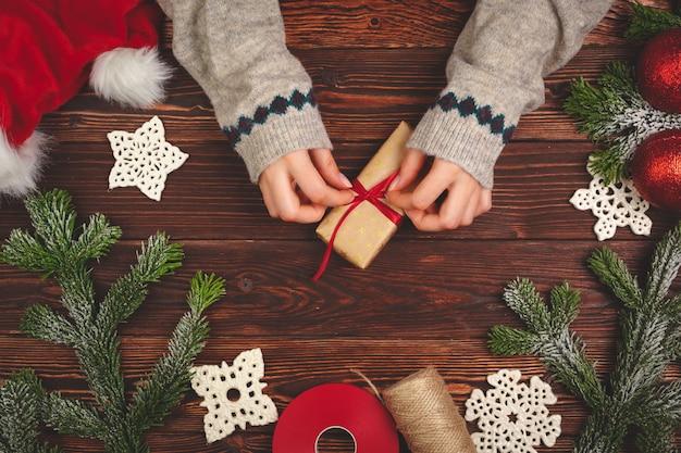 Manos en suéter con un regalo en la mesa de madera con adornos navideños