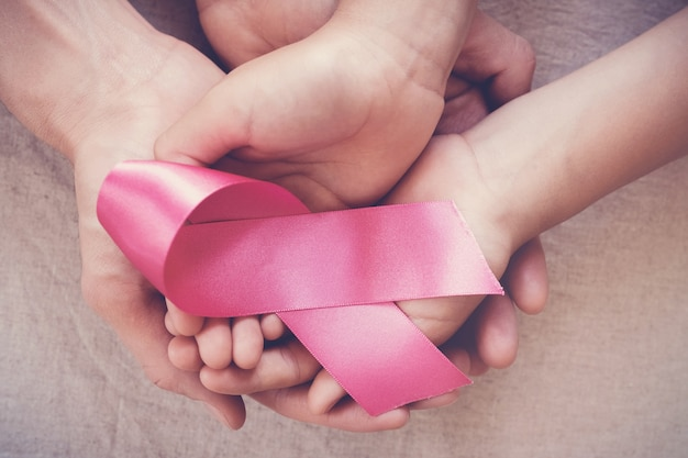 Manos sujetando cinta rosada, cáncer de mama octubre conciencia rosa