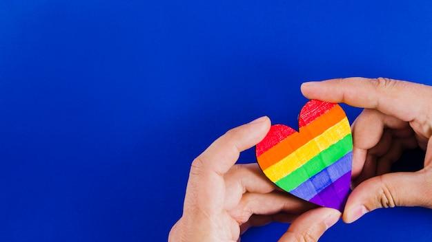 Manos sujetando un corazón con los colores de la bandera del orgullo