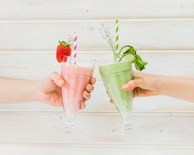 Manos sujetando deliciosos smoothies de verano