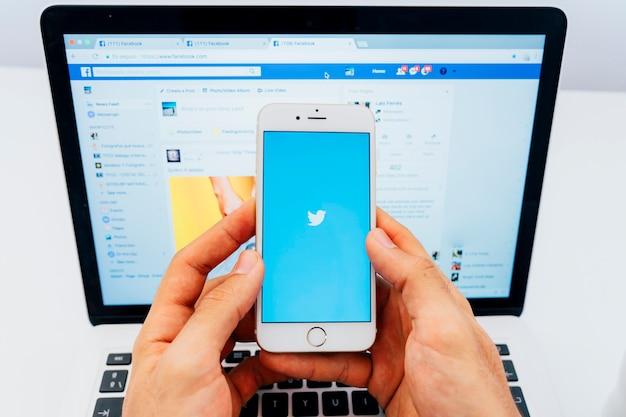 Manos sujetando el móvil con twitter y el portátil de fondo