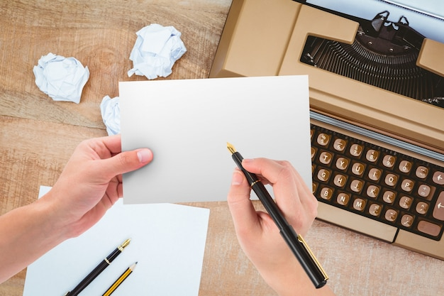 Manos sujetando un papel con máquina de escribir de fondo