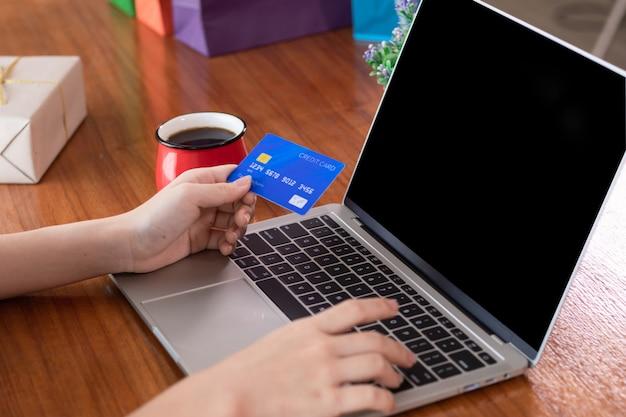 Manos con tarjeta de crédito de retención mediante computadora portátil para e-marketing o concepto de compras en línea en casa