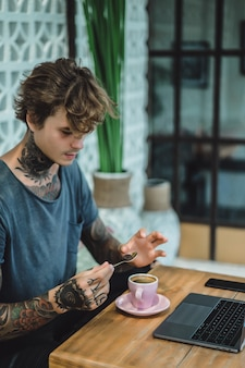 Manos tatuadas, café y computadora portátil