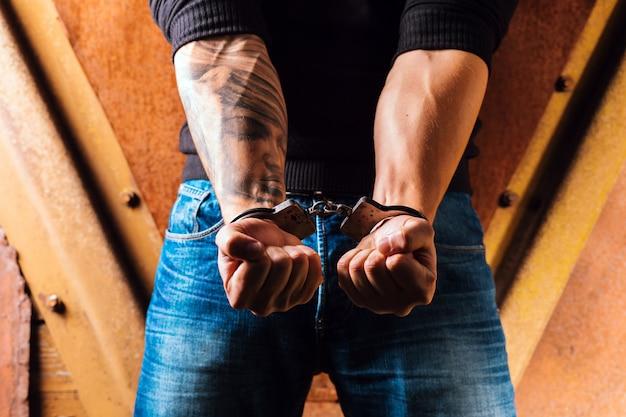 Manos tatuadas de un criminal esposado.