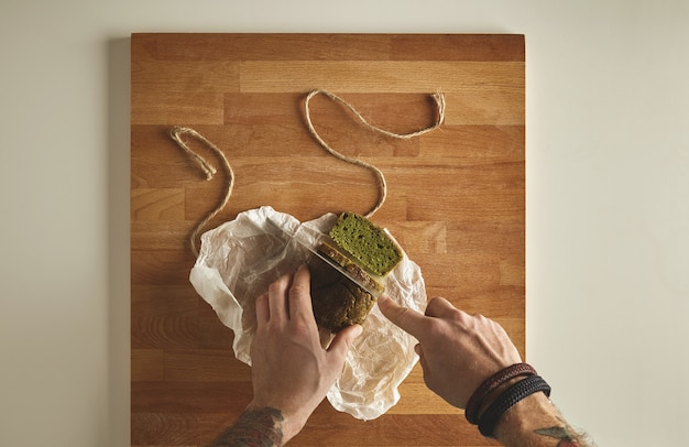 Las manos tatuadas del hombre brutal cortan el pan rústico verde casero de la espinaca sana con el cuchillo de la vendimia en rebanadas. tablero de madera vista superior de la mesa blanca