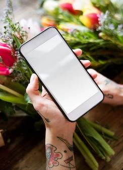 Manos tatuadas con teléfono móvil con pantalla en blanco y ramo de flores.